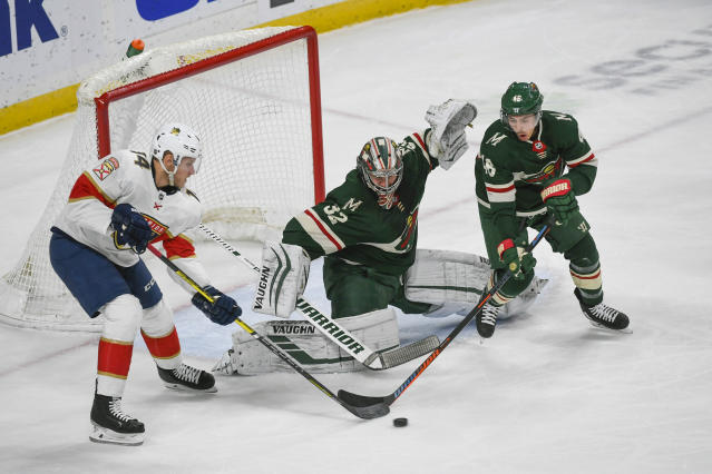 Florida Panthers center Dominic Toninato, left, and Minnesota Wild defenseman Jared Spurgeon, right, battle for control of the puck in front of Wild goalie Alex Stalockduring the first period of an NHL hockey game Monday, Jan. 20, 2020, in St. Paul, Minn. (AP Photo/Craig Lassig)
