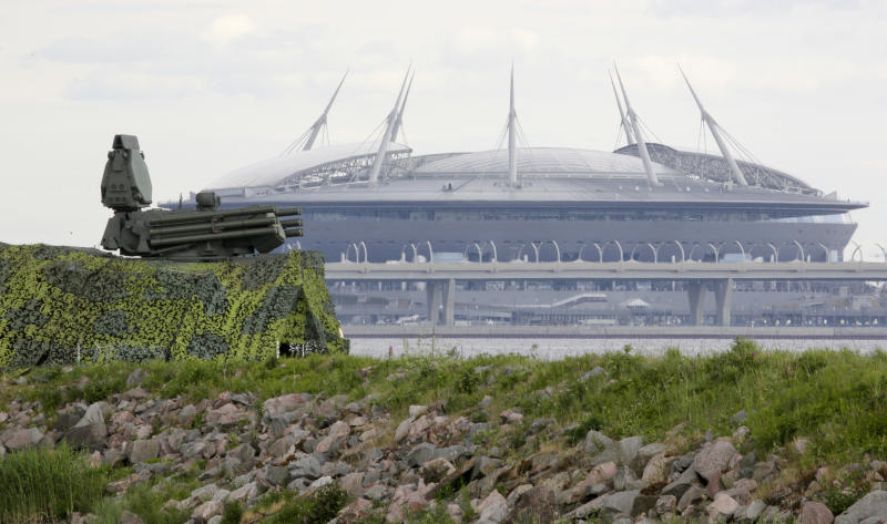 FILE - In this June 12, 2018, file photo, a Pantsir antiaircraft missile system, left, stands on guard of the air space above Saint Petersburg stadium which will host some 2018 World Cup matches in St.Petersburg, Russia. A year after hosting the World Cup, Russia is boasting the biggest club soccer crowds since Soviet days and participation at the amateur level is on the rise. Still, there are signs of trouble for the sport. (AP Photo/Dmitri Lovetsky, File)