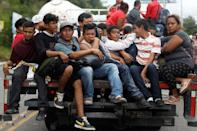 Honduran migrants, part of a caravan trying to reach the U.S., are seen on a truck during a new leg of her travel in Zacapa, Guatemala October 17, 2018. REUTERS/Edgard Garrido