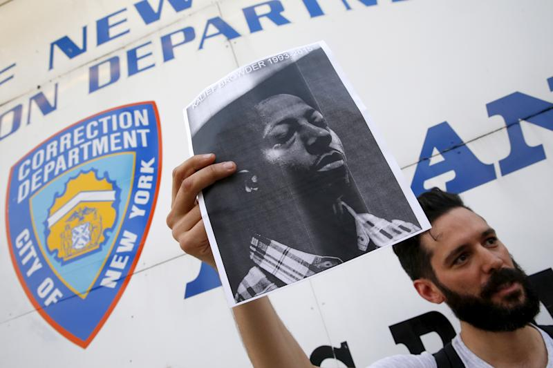 A demonstrator holds a photo of Kalief Browder during a candlelight vigil outside the entrance to the Rikers Island correctional facility in the Queens borough of New York June 11, 2015. New York City Mayor Bill de Blasio on Monday vowed to push reforms at the city's troubled Rikers Island prison complex after the reported weekend suicide of the 22-year-old Browder who had been held there for three years without being convicted of a crime. REUTERS/Shannon Stapleton