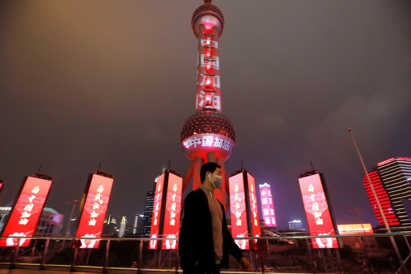 """Man wearing a face mask walks past the Oriental Pearl Tower lit with messages reading """"Stay strong China"""", on the Lantern Festival in Shanghai"""