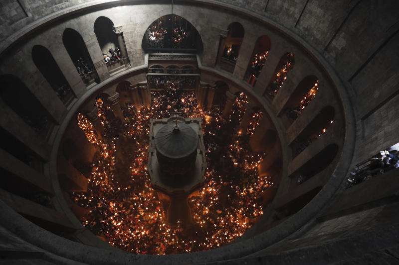 Christian pilgrims light candles during the Holy Fire ceremony in the church of the Holy Sepulchre, traditionally believed to be the burial site of Jesus Christ, Saturday, April 15, 2017, in Jerusalem. Thousands of Christians have gathered in Jerusalem for the ancient fire ceremony that celebrates Jesus' resurrection. (AP Photo/Tsafrir Abayov)