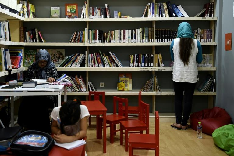 Refugees read books at a library set up by We Need Books, an international non-governmental organisation (NGO) hosting Syrian and Afghan women and children in central Athens