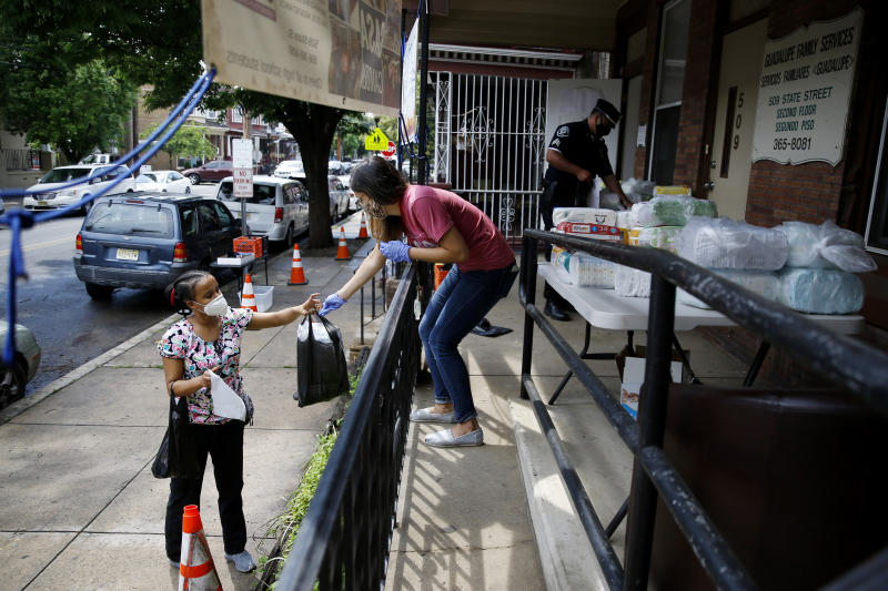 In this June 11, 2020, photo Lourdes Sherby, center, with Guadalupe Family Services, hands diapers to Louisa Peralta in Camden, N.J.