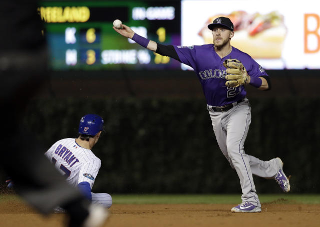 Colorado Rockies shortstop Trevor Story, right, throws out Chicago Cubs' Anthony Rizzo at first after forcing out Kris Bryant at second during the sixth inning of the National League wild-card playoff baseball game Tuesday, Oct. 2, 2018, in Chicago. (AP Photo/Nam Y. Huh)