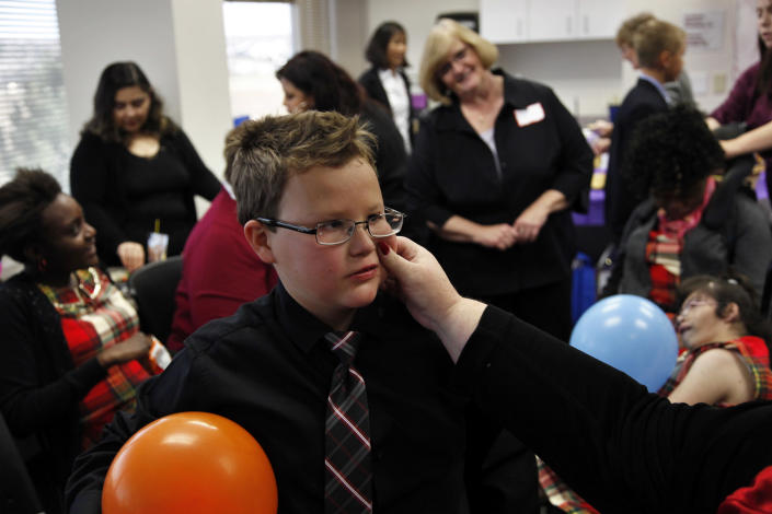 In this Nov. 14, 2012 photo, Anthony, 11, the intellectually-disabled son of Carrie Ann Lucas, gets a pinch on the cheek from his mother during a party held for newly-adopted children and their families on National Adoption Day at the Arapahoe County Justice Center in Centennial, Colo., on the day Anthony officially became her son. Carrie Ann Lucas, herself disabled, is the mother of four disabled adopted children. (AP Photo/Brennan Linsley)