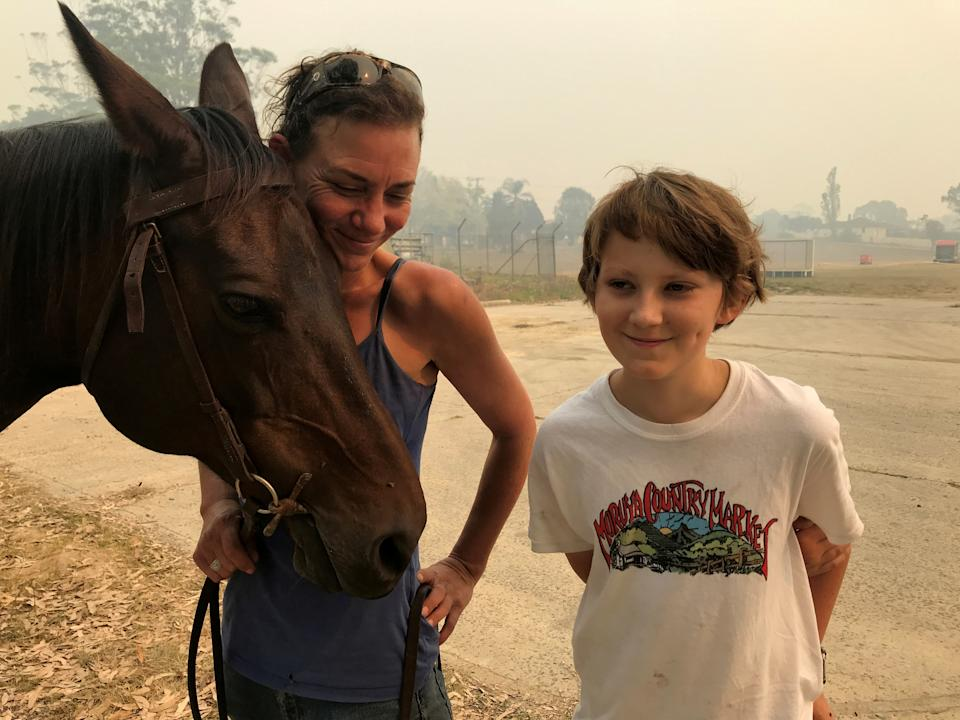 Bec Winter stands next to her son, Riley, while hugging her horse Charmer, who she rode to safety through bushfires on New Year's Eve, in Moruya, Australia January 4, 2020. REUTERS/Jill Gralow     TPX IMAGES OF THE DAY