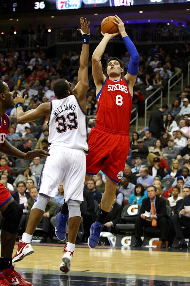 NEWARK, NJ - APRIL 10: Nikola Vucevic #8 of the Philadelphia 76ers attempts a shot in the first half against Shelden Williams #33 of the New Jersey Nets at Prudential Center on April 10, 2012 in Newark, New Jersey. NOTE TO USER: User expressly acknowledges and agrees that, by downloading and or using this photograph, User is consenting to the terms and conditions of the Getty Images License Agreement. (Photo by Chris Chambers/Getty Images)