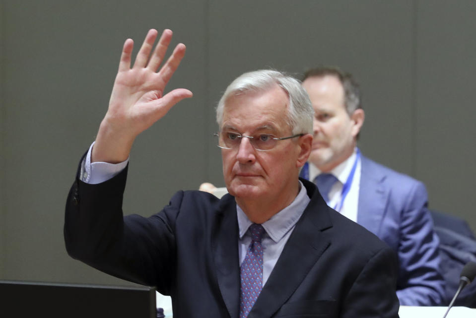 European Commission's Head of Task Force for Relations with the United Kingdom Michel Barnier raises his hand during a meeting of ambassadors of European Union governments in Brussels, Monday, Dec. 14, 2020. Teetering on the brink of a no-deal Brexit departure, Britain and the European Union stepped back from the void Sunday and agreed to continue trade talks, although both downplayed the chances of success. (Yves Herman, Pool Photo via AP)