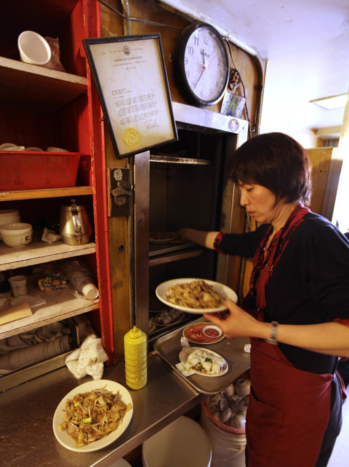 """Waitress Fanny He pulls meals out of a dumbwaiter to serve on an upstairs floor during lunch at the Sam Wo restaurant in Chinatown in San Francisco, Friday, April 20, 2012. The 100-year-old Chinese restaurant known for having """"the world's rudest waiter"""" is shutting its doors and serving its last customers Friday. (AP Photo/Eric Risberg)"""
