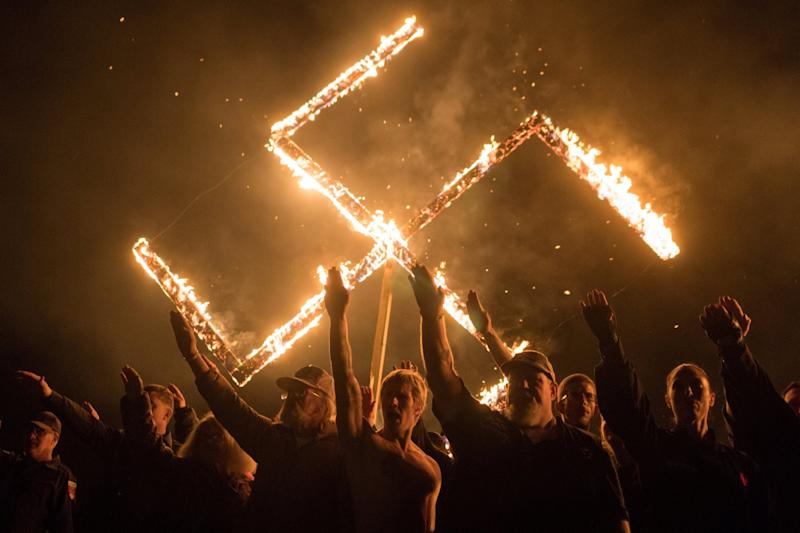 Supporters of the National Socialist Movement, a white nationalist political group, give Nazi salutes while burning a swastika in Georgia, US: Reuters