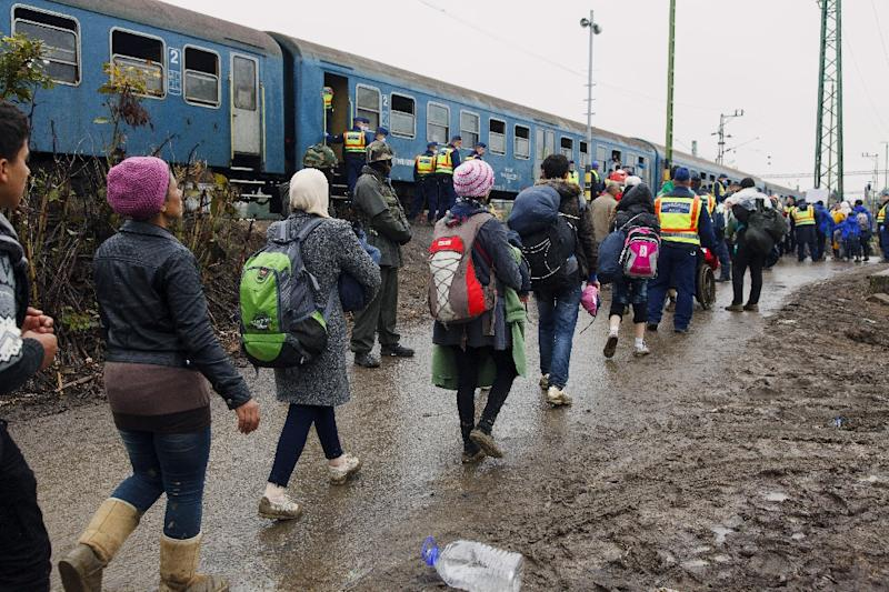 Migrants board a train after making their way through the countryside and crossing the Hungarian-Croatian border near the village of Zakany on October 16, 2015