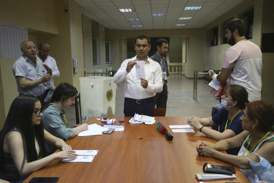 Election officials count ballots at a polling station after parliamentary elections in Yerevan, Armenia, Sunday, June 20, 2021. Armenians are voting in a national election after months of tensions over last year's defeat in fighting against Azerbaijan over the separatist region of Nagorno-Karabakh. (Hayk Baghdasaryan/PHOTOLURE via AP)
