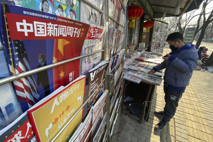 A newsstand vendor looks through his display near a magazine with a cover depicting U.S. President Joe Biden near U.S. and Chinese flags in Beijing on Thursday, Jan. 21, 2021. As a new U.S. president takes office, he faces a determined Chinese leadership that could be further emboldened by America's troubles at home. (AP Photo/Ng Han Guan)