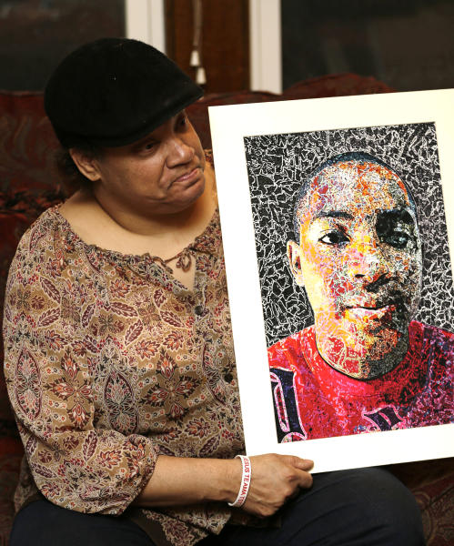 Lisa Williamson holds up a self-portrait of her son Brandon Murray, Monday, March 11, 2013, in Warren, Ohio. Investigators spent Monday trying to piece together why eight teenagers were crammed into a speeding SUV without the owner's permission when it flipped over into a pond, killing six of them, including Murray. (AP Photo/Tony Dejak)