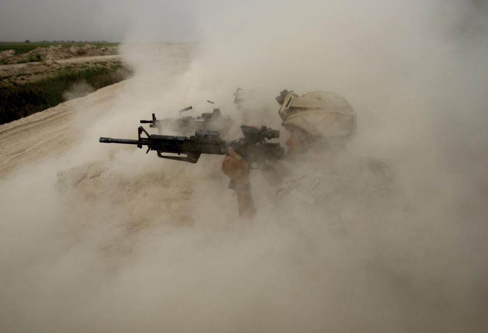 U.S. Marines, from the 24th Marine Expeditionary Unit, return fire on Taliban positions near the town of Garmser in Helmand Province of Afghanistan on May 2, 2008. (AP Photo/David Guttenfelder, File)