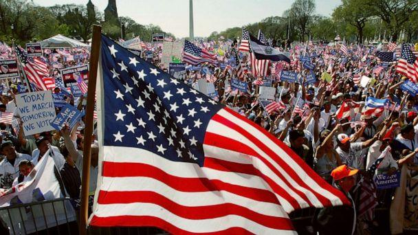 PHOTO: A U.S. flag flies as demonstrators rally during the National Day of Action for Immigrant Justice, or La Marcha, on the National Mall April 10, 2006 in Washington, DC. (Win Mcnamee/Getty Images)