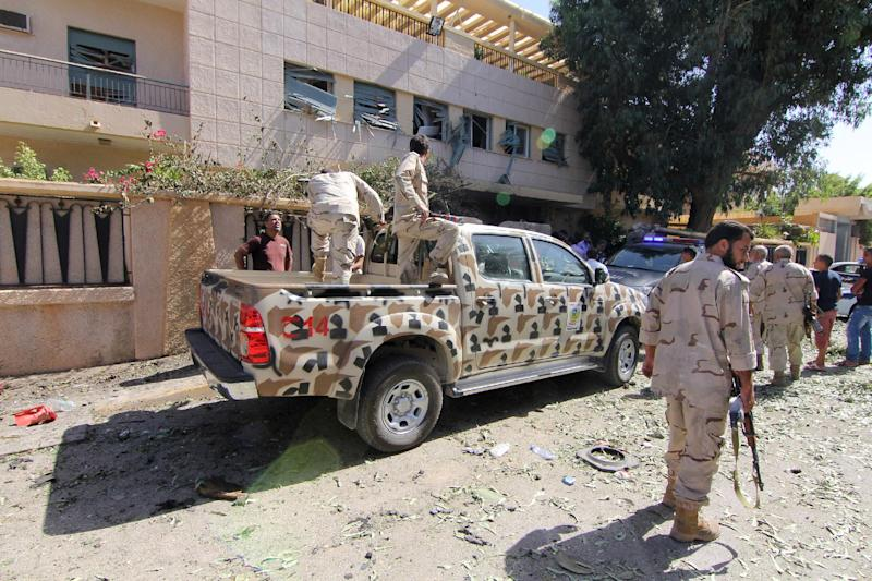 Security forces work at the site where a car bomb went off outside the building housing Swedish and Finnish consulates on Friday, Oct. 11, 2013 in Libya's eastern city of Benghazi, badly damaging the building, but leaving no casualties. Benghazi has been hit by a wave of attacks against government offices and targeted killings in recent months as security agencies struggle to secure Libya since the 2011 civil war. Weapons have proliferated and a number of militias have vied for authority, operating with impunity.(AP Photo/Mohammed el-Shaiky)