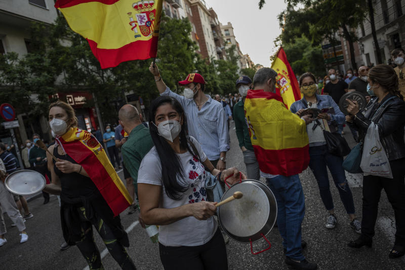 People take part in a protest against the Spanish government amid the lockdown to prevent the spread of coronavirus in Madrid, Spain, Monday, May 18, 2020. New infections and deaths have slowed considerably in Europe, where some countries started easing lockdowns a month ago and even the harshest shutdowns — such as those in Italy and Spain — have loosened significantly. (AP Photo/Bernat Armangue)