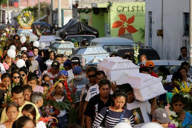 <p>People accompany caskets, holding the bodies of victims who died in an earthquake, through the streets in Atzala, on the outskirts of Puebla, Mexico, Sept. 20, 2017. (Photo: Imelda Medina/Reuters) </p>