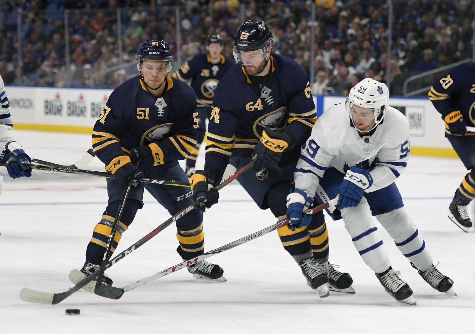 FILE - Buffalo Sabres center Kyle Criscuolo (51), right wing Tyler Randell (64) and Toronto Maple Leafs right wing Jeremy Bracco (59) battle for the puck during the second period of an NHL preseason hockey game in Buffalo, N.Y., in this Saturday, Sept. 22, 2018, file photo. Former minor league hockey player Ty Randell turned down a contract offer to pursue a career in firefighting. Randell went to firefighting school as part of the Professional Hockey Players Association's career enhancement program. (AP Photo/Adrian Kraus, File)