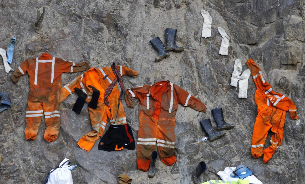 Clothing used by miners dry on a rock wall outside the entrance of the Cabeza de Negro gold-and-copper mine where some miners are trapped in Yauca del Rosario, Peru, Tuesday April 10, 2012. Authorities say nine miners trapped inside the wildcat mine since April 5 are being supplied with sports drinks, soup and food while emergency responders work to free them. (AP Photo/Martin Mejia)