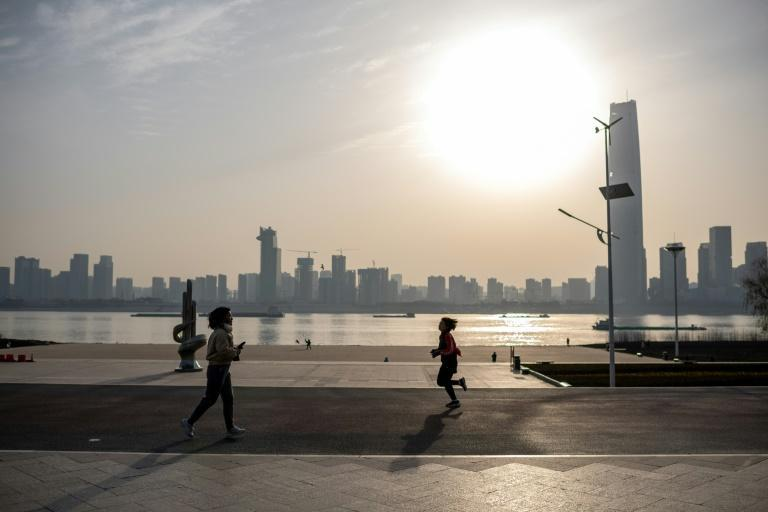 People run along the banks of the Yangtze River in Wuhan on the first anniversary of China confirming its first death from the COVID-19 coronavirus
