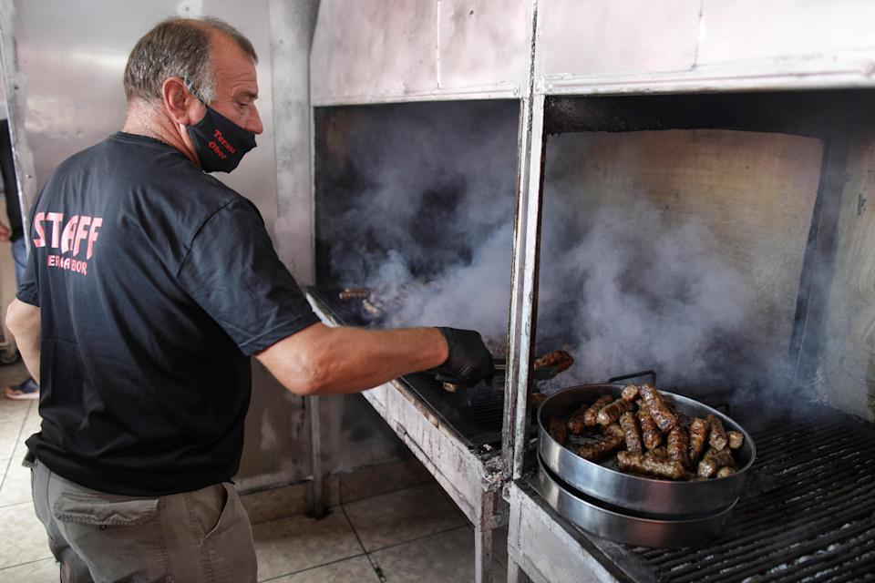 A man grills traditional Romanian minced meat rolls called 'mici' in Bucharest