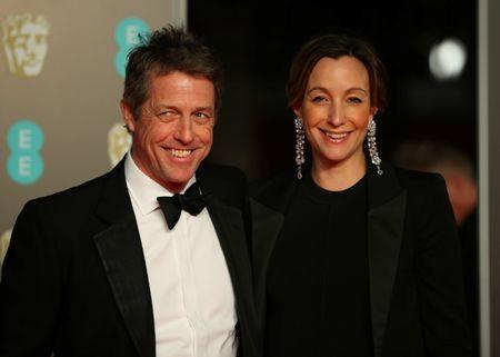 FILE PHOTO - Hugh Grant and Anna Eberstein arrive for the British Academy of Film and Television Awards (BAFTA) at the Royal Albert Hall in London, Britain, February 18, 2018. REUTERS/Hannah McKay