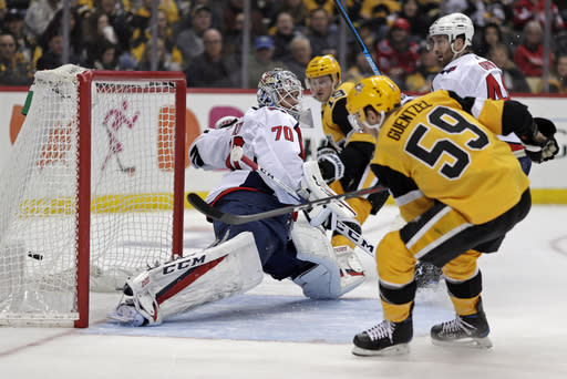 Pittsburgh Penguins' Jake Guentzel (59) gets a shot behind Washington Capitals goaltender Braden Holtby (70) for a goal in the second period of an NHL hockey game in Pittsburgh, Tuesday, March 12, 2019. (AP Photo/Gene J. Puskar)