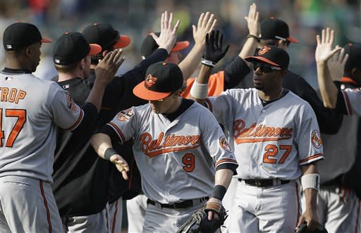 Baltimore Orioles, including Nate McLouth (9) and Endy Chavez (27), celebrate at the end of a baseball game against the Oakland Athletics, Sunday, Sept. 16, 2012, in Oakland, Calif. The Orioles won 9-5.(AP Photo/Ben Margot)