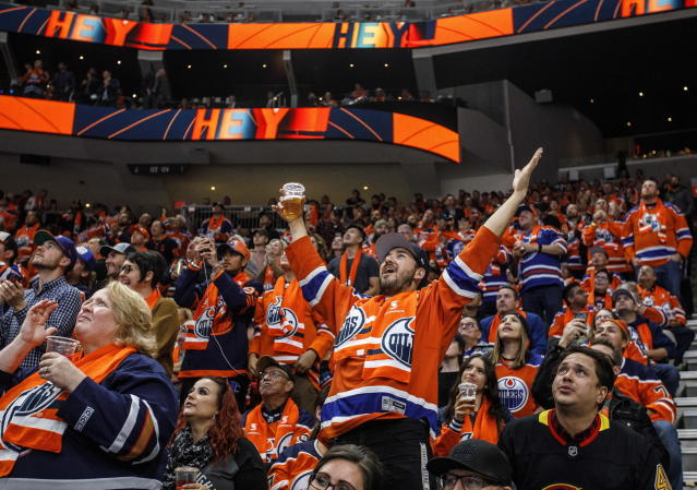 FILE - In this Oct. 2, 2019, file photo, Edmonton Oilers fans celebrate a goal against the Vancouver Canucks during the first period of an NHL hockey game in Edmonton, Alberta. Many NHL issues are similar to those facing North America's other major professional leagues, such as when fans will be allowed to attend games. Others are more distinct to hockey, such as the effect the drop of the Canadian dollar will have on a league with seven of its 31 teams based north of the border. (Jason Franson/The Canadian Press via AP, File)