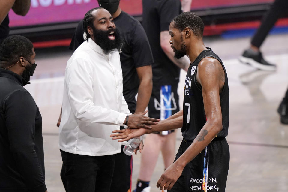 Injured Brooklyn Nets player James Harden, center left, greets Nets forward Kevin Durant (7) at the end of the third quarter of Game 2 of an NBA basketball second-round playoff series against the Milwaukee Bucks, Monday, June 7, 2021, in New York. (AP Photo/Kathy Willens)