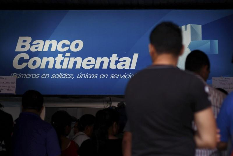 People stand outside a branch of Banco Continental, hours after the Honduran government ordered its liquidation, in Tegucigalpa
