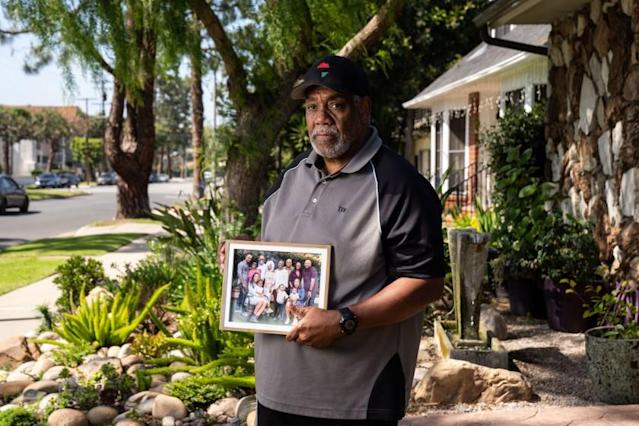 "Tony Wafford, with a photo of extended family members, outside his home in Inglewood. <span class=""copyright"">(Kent Nishimura/Los Angeles Times)</span>"
