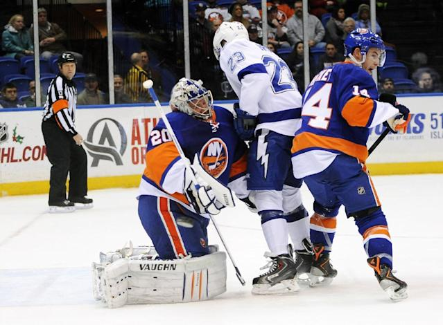 The puck flies by New York Islanders goalie Evgeni Nabokov (20) as he collides with Tampa Bay Lightning J.T. Brown (23) as New York Islanders' Thomas Hickey (14) defends in the first period of an NHL hockey game on Tuesday, Dec. 17, 2013, in Uniondale, N.Y. (AP Photo/Kathy Kmonicek)