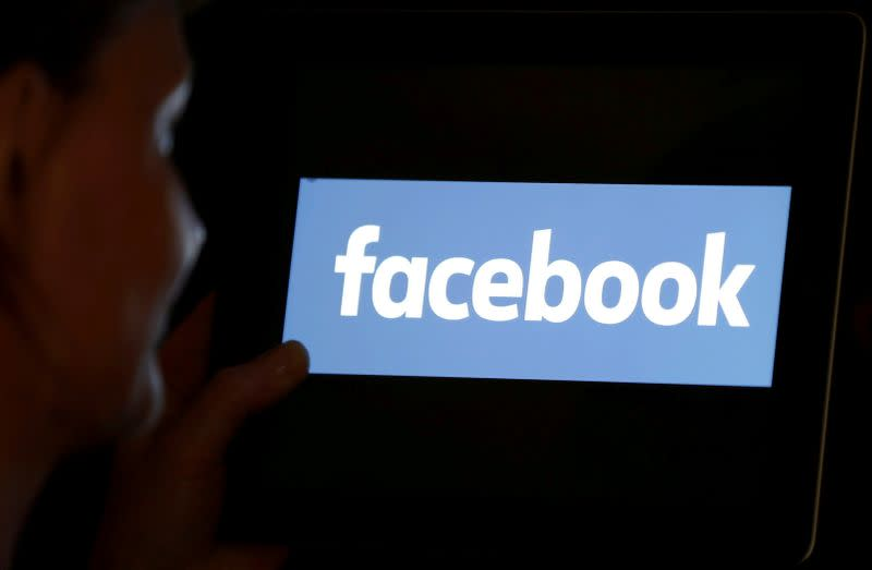 FILE PHOTO: A woman looks at the Facebook logo on an iPad in this photo illustration