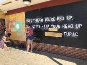 """Volunteers paint murals with lyrics from late hip-hop artist Tupac on boarded-up businesses in Kenosha, Wis., on Sunday, Aug. 30, 2020, at an """"Uptown Revival."""" The event was meant to gather donations for Kenosha residents and help businesses hurt by violent protests that sparked fires across the city following the police shooting of Jacob Blake. (AP Photo/ Russell Contreras)"""