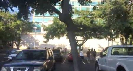 Students run for cover after an emergency alarm was sounded, at a carpark in the University of Hawaii, Honolulu, Hawaii