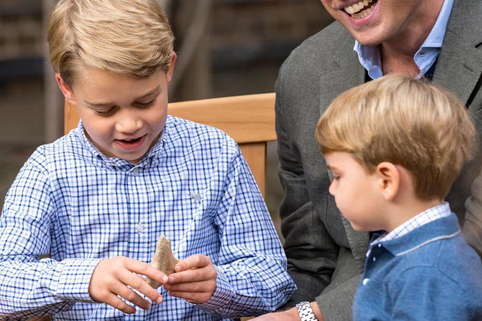 Prince George holding the giant shark tooth that was given to him by Sir David Attenborough: PA