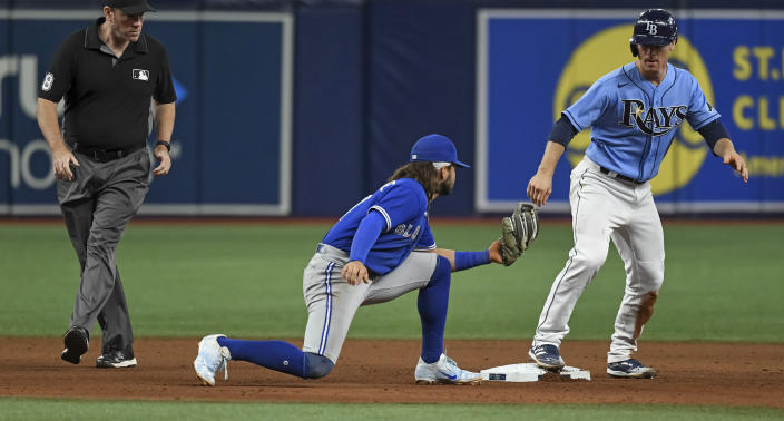 Umpire Chris Conroy, left, watches as Tampa Bay Rays' Joey Wendle, right, stands on second base as Toronto Blue Jays shortstop Bo Bichette is late with the tag during the seventh inning of a baseball game Friday, July 9, 2021, in St. Petersburg, Fla.(AP Photo/Steve Nesius)