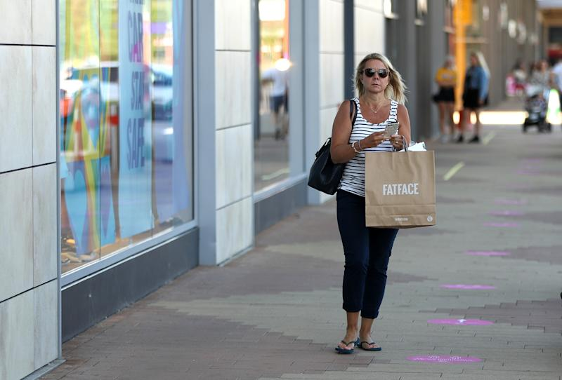 RUSHDEN, UNITED KINGDOM - JUNE 15: A shopper carry goods bought at the Fat Face store at the Rushden Lakes shopping complex on June 15, 2020 in Rushden, United Kingdom. The British government have relaxed coronavirus lockdown laws significantly from Monday June 15, allowing zoos, safari parks and non-essential shops to open to visitors. Places of worship will allow individual prayers and protective facemasks become mandatory on London Transport. (Photo by David Rogers/Getty Images)