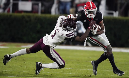 Mississippi State cornerback Martin Emerson, left, tackles Georgia wide receiver George Pickens during the first half of an NCAA college football game Saturday, Nov. 21, 2020, in Athens, Ga. (AP Photo/Brynn Anderson)