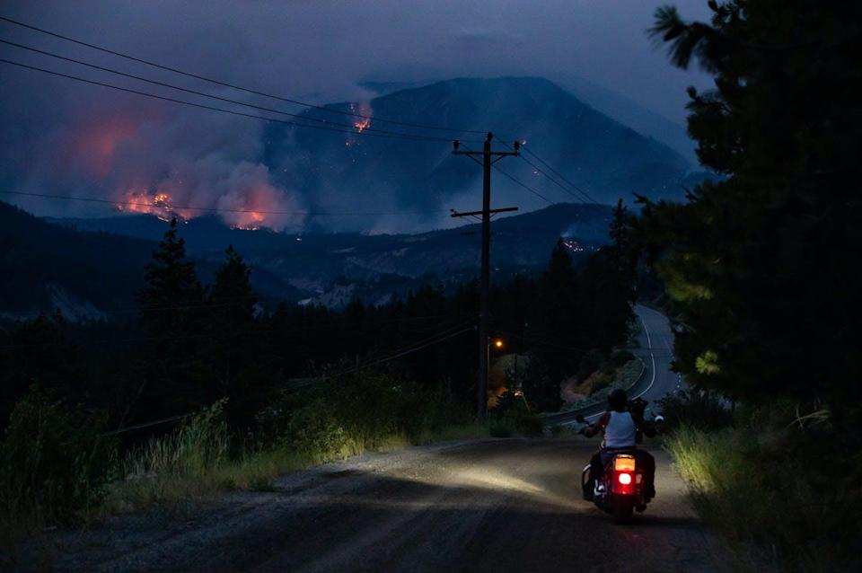 """<span class=""""caption"""">A man from Skuppah Indian Band rides off on his motorcycle after stopping to watch a wildfire burn on the side of a mountain in Lytton, B.C., in July 2021. </span> <span class=""""attribution""""><span class=""""source"""">THE CANADIAN PRESS/Darryl Dyck</span></span>"""