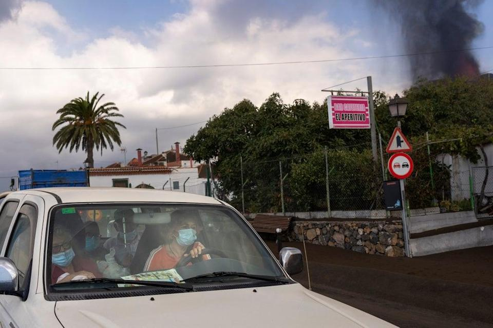 Residents leave their house in La Mancha on the island of La Palma in the Canaries (AP)