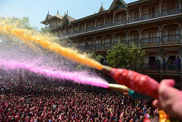 Indian Hindu devotees are sprayed with colored water by the heir to the Kalupur Swaminarayan Temple Lalji Maharaj Shri Vrajendraprasdaji Maharaj as they celebrate the Holi festival at the Swaminarayan Temple in Ahmedabad on March 13, 2017. The Hindu festival of Holi, or the 'Festival of Colors' heralds the arrival of spring and the end of winter.