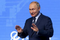 Russian President Vladimir Putin gestures as he arrives to attend the plenary session of the Russian Energy Week in Moscow, Russia, Wednesday, Oct. 13, 2021. (Sergei Ilnitsky/Pool Photo via AP)