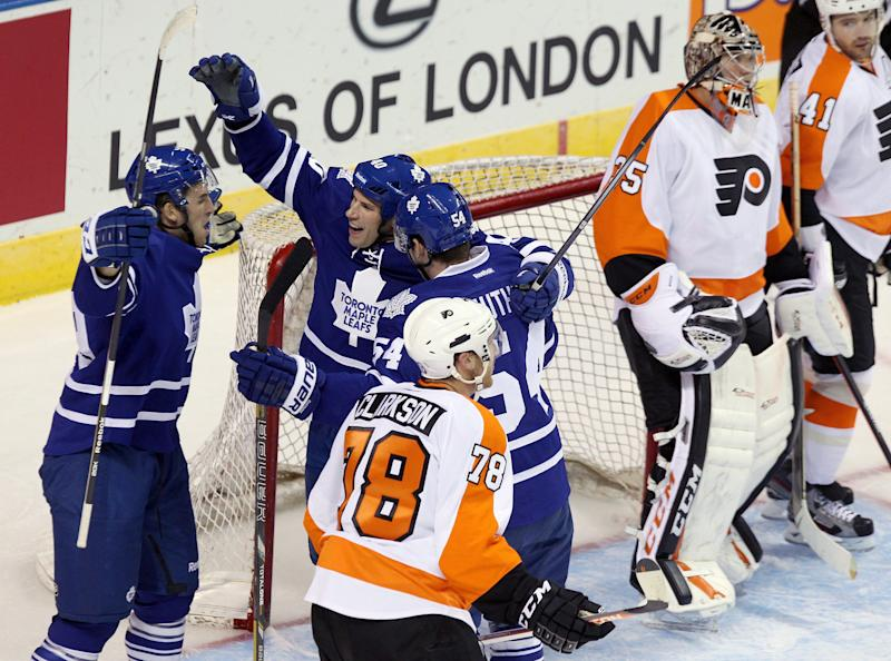 From left to right, Toronto Maple Leafs' Jamie Devane, Troy Brodie and Frederik Gautier celebrate Brodie's goal on Philadelphia Flyers' goalie Steve Mason, second from right, during first-period NHL hockey preseason game action on Sunday, Sept. 15, 2013, in London, Ontario. (AP Photo/The Canadian Press, Dave Chidley)