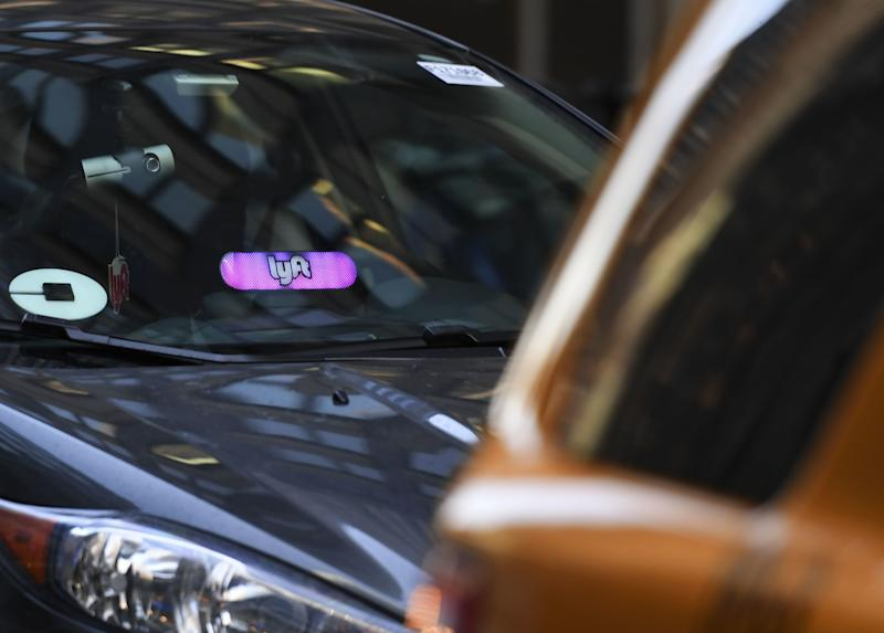 A Lyft ride-sharing car(L) is seen on Park Avenue in New York City March 26, 2019. - Lyft Inc.'s initial public offering is expected to have its (IPO) this week making it the first of the ride-hailing companies to open up to the public. (Photo by TIMOTHY A. CLARY / AFP) (Photo credit should read TIMOTHY A. CLARY/AFP/Getty Images)