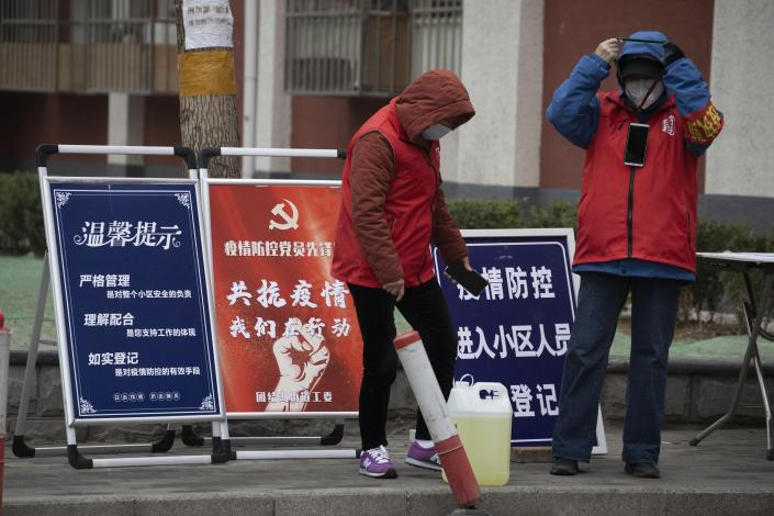 """In this photo taken Sunday, March 8, 2020, community workers stand near propaganda board which reads """"Outbreak Prevention and Control, Communist Party Member Pioneer station"""" in Beijing. As the rest of the world grapples with a burgeoning virus outbreak, China's ruling Communist Party has turned to its propaganda playbook to portray its leader as firmly in charge, leading an army of health workers in a """"people's war"""" against the disease. (AP Photo/Ng Han Guan)"""